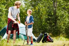 Helping father. Cute boy helping his father or elder brother to prepare everything for bonfire before cooking dinner during backpack trip Royalty Free Stock Images