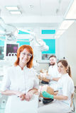 Helping future dentists master practical skills. Stomatology academic teacher in a fully-equipped classroom with her students stock images