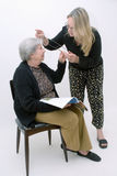 Helping Grandma with her Glasses. Woman helping her mother with her reading glasses. Isolated against a white background Stock Photos
