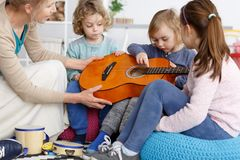 Helping with guitar. Kindergarten teacher helping little kids to play the guitar stock photography