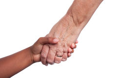 Helping hand. Young dark skinned mixed race girls hand, holding older senior woman's hand isolated against white background including clipping path stock photo