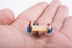 Helping hand. Miniatures seated at a table on top of a hand Stock Photos