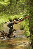 Helping Hand. A father helps his son safely across a stream Stock Image