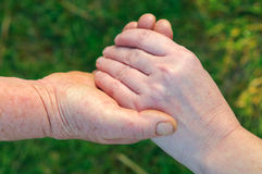 Helping hand. Old worked hand holding an other younger female hand on green background royalty free stock photo