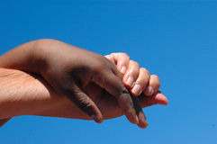 Helping hand. An old caucasian white hand and a young African American black hand holding and helping each other in front of blue sky background Royalty Free Stock Images