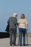 A Helping Hand. Elderly man helping a middle aged female to walk with walking sticks, with a blue sky to the rear Royalty Free Stock Image