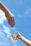 Helping hand. One adult hand reaches out to help child hand in need Royalty Free Stock Images
