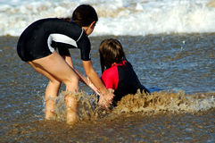 Helping hand. Kids playing in the sea Royalty Free Stock Images