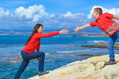 Helping hand. Mother and son reaching for each other, stretching hands toward each other with sea and clouds in the background. They long to be together They are Stock Image