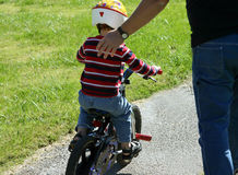 Helping hand. Young boy riding on his bike stock photography