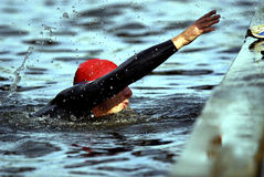 A helping hand. Triathlete at the end of a grueling river swim reaching up to exit the water Stock Photography
