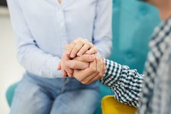 Helping Hand. Close up of two people holding hands in  therapy session or support group, copy space royalty free stock photos