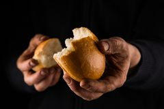 Helping hand giving a piece of bread. Poor Man sharing Bread, Helping Hand Concept. In color royalty free stock photos