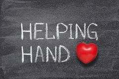 Helping hand heart. Helping hand phrase written on chalkboard with red heart symbol stock images