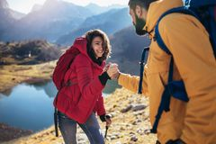 Hiker woman getting help on hike happy overcoming obstacle stock images
