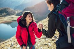 Hiker woman getting help on hike happy overcoming obstacle royalty free stock image