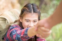 Helping hand - hiker woman getting help on hike smiling happy ov Stock Images