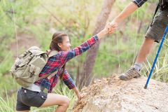 Helping hand - hiker woman getting help on hike smiling happy overcoming obstacle. Tourist walking on the Mountain, Young couple. Traveling stock photos
