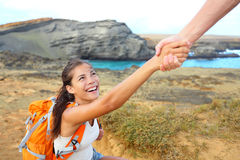 Helping hand - hiker woman getting help on hike. Helping hand - hiker women getting help on hike smiling happy overcoming obstacle. Tourist backpackers walking royalty free stock photos