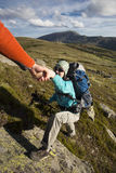 Helping hand. Helping hand - hiker women getting help on hike smiling happy overcoming obstacle stock photo
