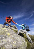 Helping hand. Helping hand - hiker women getting help on hike smiling happy overcoming obstacle royalty free stock photo