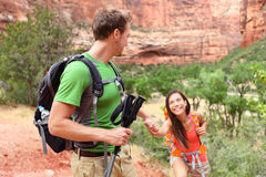 Helping hand - hiking woman getting help on hike Stock Photo