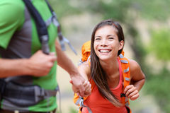 Helping hand - hiking woman getting help on hike. Helping hand - hiking women getting help on hike smiling happy overcoming obstacle. Active lifestyle hiker stock photography