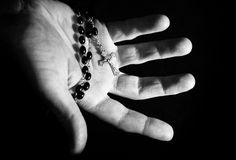 Helping hand. Holding onto rosary beads and cross Stock Photos