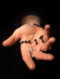 Helping hand. Holding onto rosary beads and cross Stock Photo