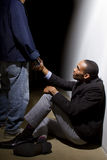 A Helping Hand. Man helping a depressed fellow by offering a helping hand stock photography