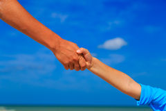 Helping hand of mother and child on sky at the beach Royalty Free Stock Image
