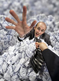 Helping hand saving buried businessman. Helping hand saving businessman buried in big heap of crumpled papers Royalty Free Stock Images