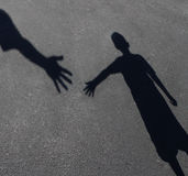 Helping Hand. With a shadow on pavement of an adult hand offering help or therapy to a child in need as an education concept of charity towards needy kids and Royalty Free Stock Photo