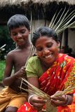 Helping hand to Mother. A tribal woman making handicraft with her child Stock Photography