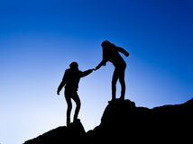 Helping hand between two climber. Silhouette of helping hand between two climber Royalty Free Stock Photo