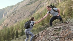 Helping hand between two climbers. two tourists on top of a mountain, a man helps a woman climb a steep stone. Mutual. Help stock footage
