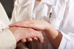 Helping hands. The nurse holds hands of the elderly female stock photography
