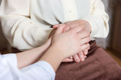 Helping hands. The nurse holds hands of the elderly female stock photo