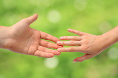 Helping hands. Two adult hands reaching to each other Stock Photo
