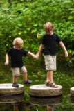 Helping Hands. An older, 5 year old brother helping his younger, 2 year old brother across a pond with stepping stones Stock Photography
