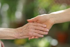 Young caregiver holding seniors hands. Helping hands, care for the elderly concept royalty free stock photos