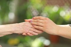 Young caregiver holding seniors hands. Helping hands, care for the elderly concept royalty free stock image
