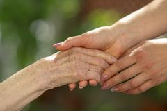 Young caregiver holding seniors hands. Helping hands, care for the elderly concept stock photography