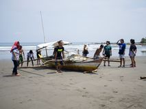 Helping hands carrying a fishing boat from the sea royalty free stock photography