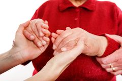 The helping hands. Close up photo of young caregiver holding elderly woman hands Royalty Free Stock Photos