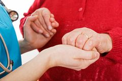 The helping hands. Close up photo of young caregiver holding elderly woman hands Stock Image
