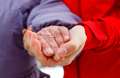 The helping hands. Close up photo of young caregiver holding the elderly woman hand Stock Photo