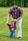 Helping Hands. Father helping toddler son to learn how to walk in an outdoor setting stock images
