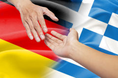 Helping hands with german and greece flags Royalty Free Stock Image