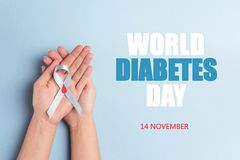 Helping hands holding blue ribbon awareness with red blood drop. On a blue background. World diabetes day,14 november. Copy space, top view royalty free stock image